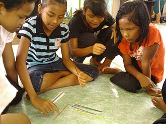 Jakun people - Jakun teenagers playing pick-up sticks in a community centre.