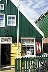 foto van Perceelsgedeelte van een houten huis met aan de straatzijde een bakstenen pui