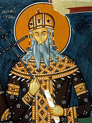Grey-bearded king, holding a scroll and a cross-shaped staff