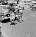 Mannelijke en een vrouwelijke agente staan voor een stilstaande auto terwijl de , Bestanddeelnr 255-2017.jpg