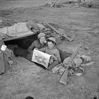 Ireland's Saturday Night - Men of the 2nd Royal Inniskilling Fusiliers reading Ireland's Saturday Night in their foxhole in the Anzio bridgehead, 17 March 1944