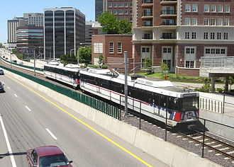 Clayton, Missouri - A Blue Line MetroLink train bound for Shrewsbury-Lansdowne I-44 station passes by downtown Clayton.  The train is travelling within the median of Forest Park Parkway.