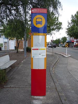 Buses in Sydney - Metrobus blade stop sign at Chester Hill with the name of the stop and a red lower section indicating that the stop is served by Metrobuses