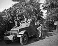 Militairen met wapens in de aanslag zitten op of staan bij een pantserwagen (M3 , Bestanddeelnr 10545.jpg