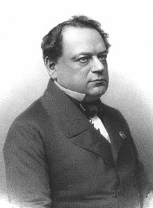 Photograph of a lithograph. It shows the torso and head of a middle-aged man who is apparently seated and is looking off to the reader's right. He is dressed formally, and is wearing a coat, a white shirt, and a tie. There is a metal pin on his lapel. He has black hair, is somewhat balding, and is slightly overweight.