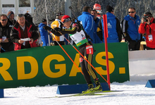 A woman stands on cross country skies, pictured from the side. She skies in an upright position leaning slightly forward onto her ski poles. She wears a red cap, a white and green jersey and black trousers and has a rifle on her back. An advertising board with ten people behind it can be seen in the background.