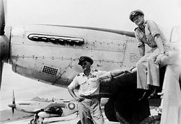 Two men in military uniforms and peaked caps, with a single-engined fighter plane