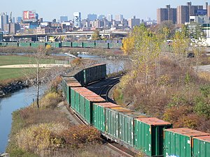 Oak Point Link - Oak Point Link looking northwest from Triboro Bridge. The Harlem River Intermodal Yard is in the background. Green containers on train are for hauling municipal solid waste (trash).