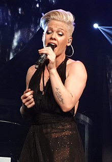 Pink with short platinum hair singing with a microphone