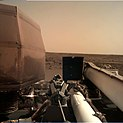 Image of the science deck of the InSight lander, with the Martian landscape in the background