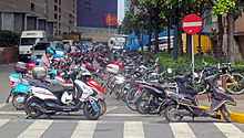 "Two rows of motorbikes, many showing their age and use, parked next to a city street corner. There is a large white-bar-on-red-circle ""do not enter"" sign at the upper right."