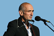 Head and shoulders of a fifty-two-year-old male standing at a microphone. He is shown in right profile, wearing a harmonica in a cradle and staring into the distance.
