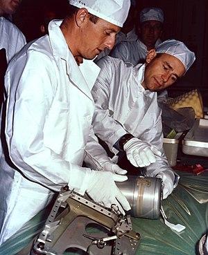 Apollo 12 Passive Seismic Experiment - Apollo 12 astronauts Pete Conrad and Al Bean examining the Passive Seismometer prior to the flight
