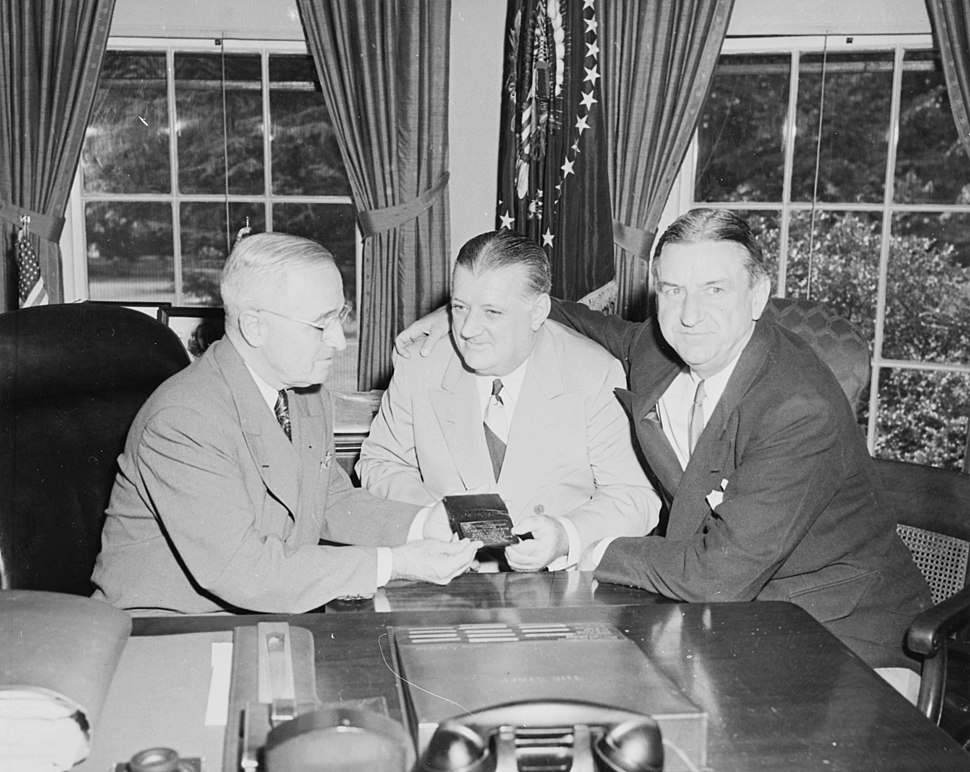 Photograph of President Truman at his desk in the Oval Office, receiving his annual pass to National Football League... - NARA - 200160