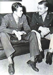 Two men, actor James Stewart and Gable are in their dress uniforms and are seated comfortably on a couch, smiling happily at each other.