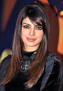 Priyanka Chopra in a black dress looking towards the camera, her dark brown hair falling straight on the side of her face