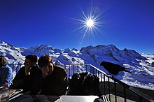 Visitors sitting at tables on a large balcony high in the Swiss Alps, and a chough is perching on a railing beside them.