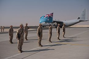 Personnel in camouflage uniforms with RAAF flag lined up in front of four-engined military cargo plane in grey livery