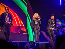 Madonna onstage wearing  a black suit. She's flanked by two male dancers dressed in a similar style. The backdrop behind them shows orange and green flashes.