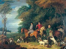 Five men and three horses at the edge of a wood along with a large group of dogs.