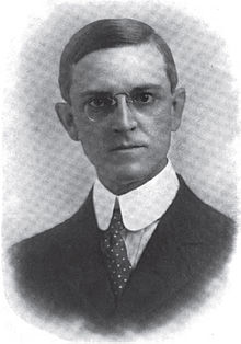 A man with dark hair wearing glasses, a high-collared white shirt, polka-dotted tie, and black jacket