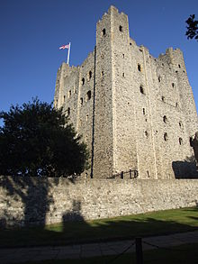 A stone tower with windows; the ones higher up are larger.