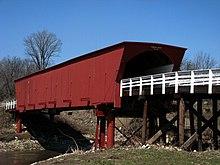 Photographie du Roseman Bridge à Madison. Le pont couvert est de couleur rouge marron, avec des barrières blanches qui le poursuivent