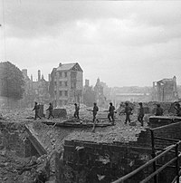 A file of soldiers walking through a blasted cityscape; only a few buildings are standing