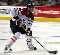 Hockey player in white Canada uniform. He guides a puck across the ice with his stick.