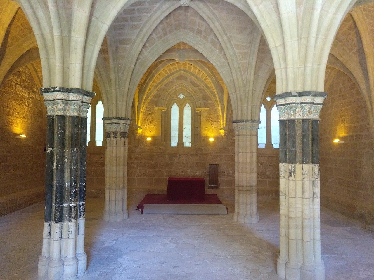 Sala Capitular del Monasterio de Piedra. Presenta 4 columnas antes policromadas, ahora descoloradas, con restos de pintura azul; al fondo, una mesa roja. Toda la sala está rodeada por un banco continuo.