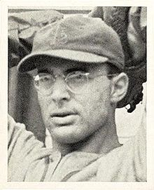 "A man wearing glasses and a dark baseball cap with an overlapping ""STL"" on the front has his hands behind his head as if preparing to throw a ball."