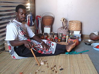 Traditional African religions - Traditional healer of South Africa performing a divination by reading the bones