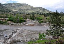 Un fiume fangoso scorre attraverso una fessura tra i resti di una diga su entrambi puntello.  Una collina boscosa o montagna sorge in background.