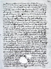 A single page from a 14th century manuscript. Un-illustrated, it is covered with dozens of lines of Latin text. The parchment is aged and has some holes in it towards the bottom, which evidently existed before the text was written around them.