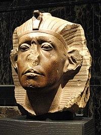 Photographie représentant une tête (en partie mutilée) de Sésostris III. Contrairement à la tradition il est représenté âgé
