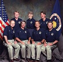 Un retrato de seis hombres y una mujer, dispuestos en dos filas, cuatro sentados al frente y tres de pie atrás.  Cada uno lleva pantalones de color canela y una camisa polo azul con un parche y su nombre, y las banderas de los Estados Unidos y la NASA son visibles en el fondo.