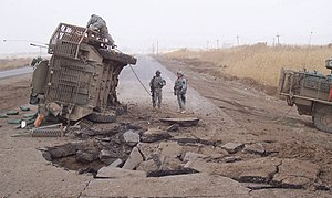 Improvised explosive device - A Stryker lies on its side following a buried IED blast in Iraq. (2007)