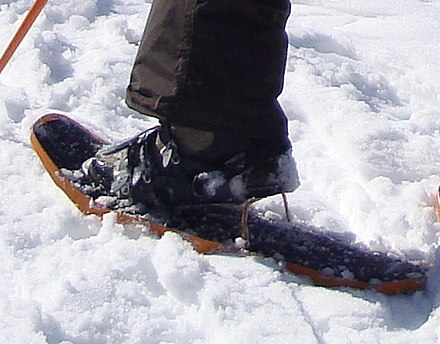 Some modern snowshoes have bars that can be flipped up for ascending steep slopes. The wearer's heel can rest on the bar. Snowshoe heel lift cropped.jpg