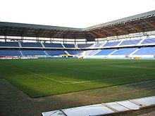 Photo de l'intérieur d'un stade vide de jour avec des panneaux publicitaires à plat au premier plan.
