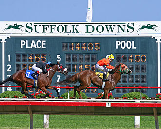 Suffolk Downs - Horses racing in front of the results board in the track infield