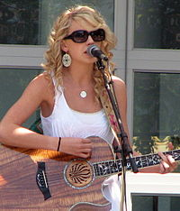 Taylor Swift, wearing a white dress and sunglasses, plays an acoustic guitar while standing at a microphone stand.