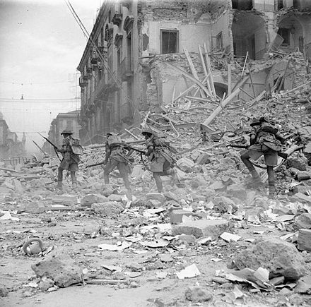 British troops scramble over rubble in a devastated street in Catania, Sicily, 5 August 1943. The British Army in Sicily 1943 NA5335.jpg