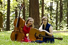 Two women sitting in woodland with a cello and a guitar.