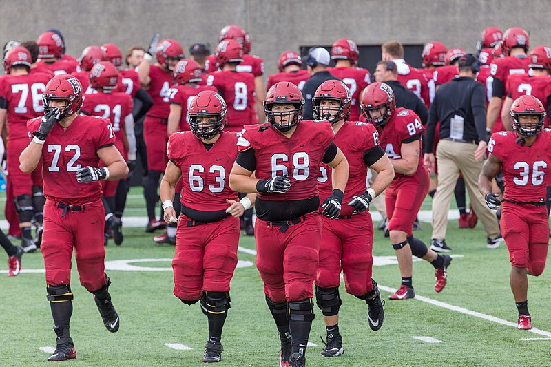 The Harvard football team takes the field.