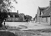 Large thatched cottage on right, man standing in front of pond on left, large thatched cottage in background with a small group of people and two horses standing nearby