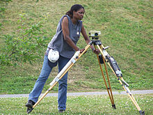 A woman setting up an optical level on a tripod.