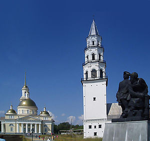 Leaning Tower of Nevyansk - The center of Nevyansk (viewer's left to viewer's right): Old Believers' church (domed), the Leaning Tower (white spire), and the monument to Peter I of Russia and Nikita Demidov (cast metal figures)