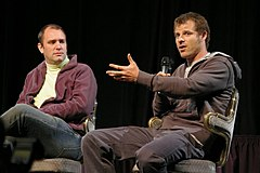 Two men sitting on chairs wearing jeans and hoodies.