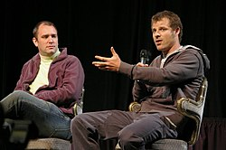 Two men sit in chairs. The man on the right holds a microphone and gestures with his left hand.