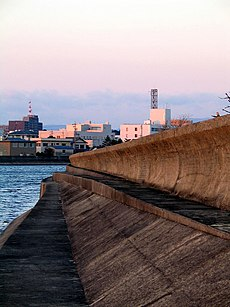 Photo of seawall, with building in background